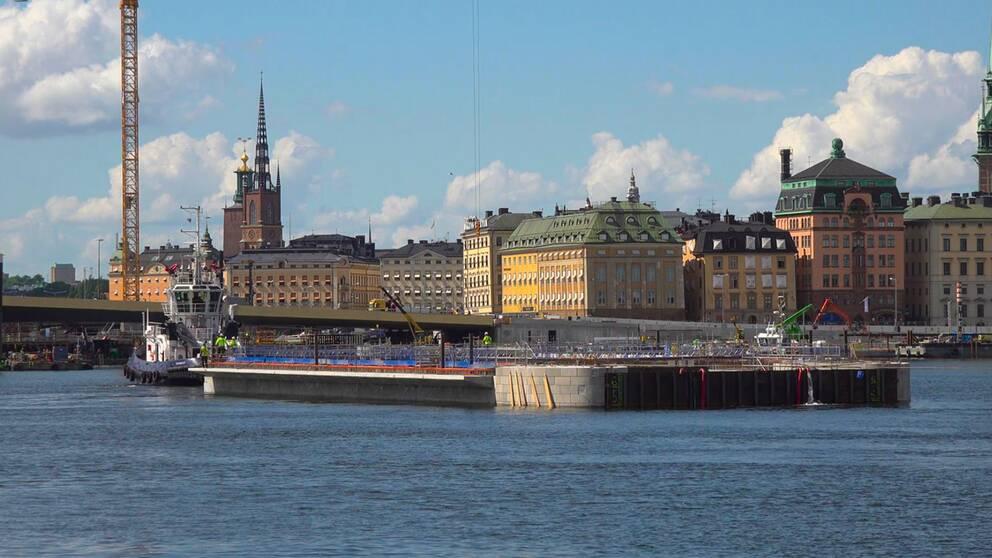 Stor båt glider in mot nya Slussenbygget. I bakgrunden skymtar Gamla Stans äldre byggnader.