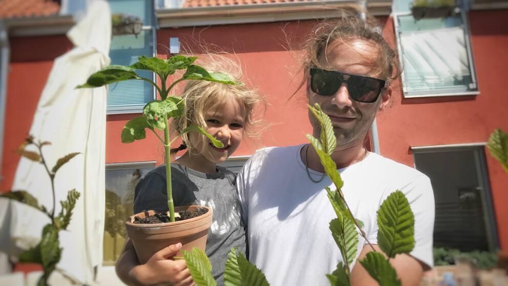 Gunnar Bange står framför sitt hus med sin dotter i famnen