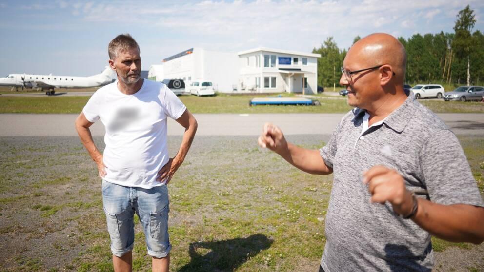 två män står och pratar ute på flygfältet i Umeå