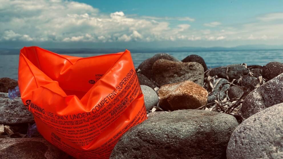 En stenstrand på Lesbos där en armpuff som man har för att flyta har