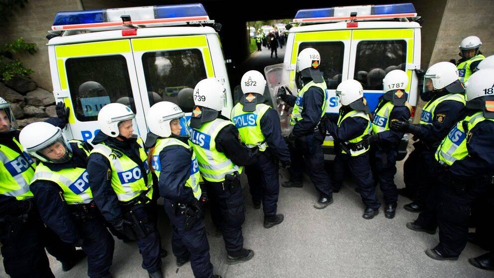 Polisstudenter övar med hjälm och skyddsväst framför två pikébussar.