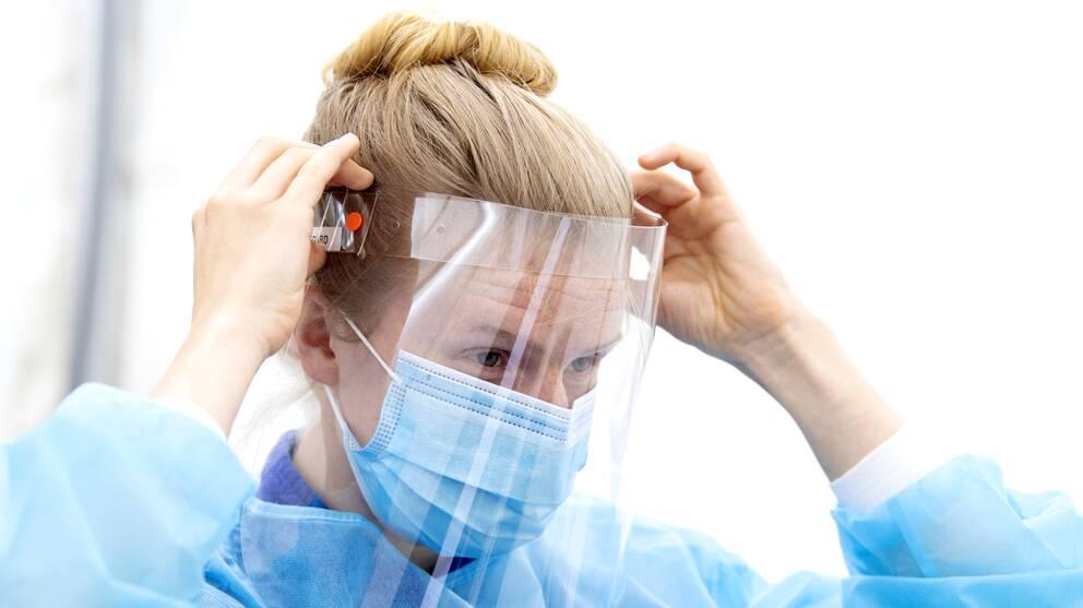 kvinna i blå sjukhusklädsel med uppsatt hår justerar skyddsvisir
