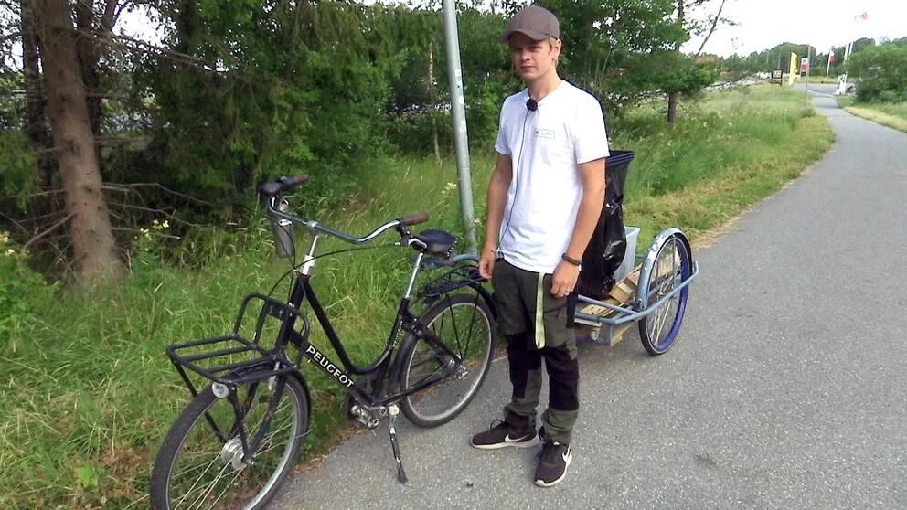 Johan Eriksson står på en cykelväg framför sin cykel och kärra.