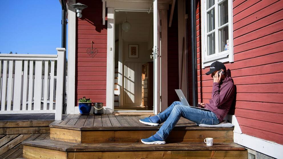 Man med bärbar dator jobbar hemifrån på sin altan.