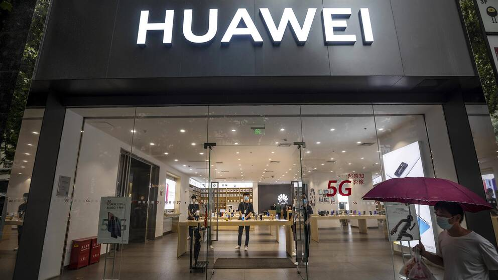 Bild tagen underifrån. En man med munskydd och paraply passerar skyltfönstret på en Huawei-butik.