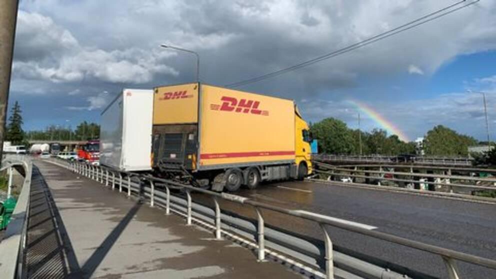 En DHL-lastbil står på tvären på motorvägen och har krockat in i broräcket. Bakom lastbilen står fler bilar i kö.