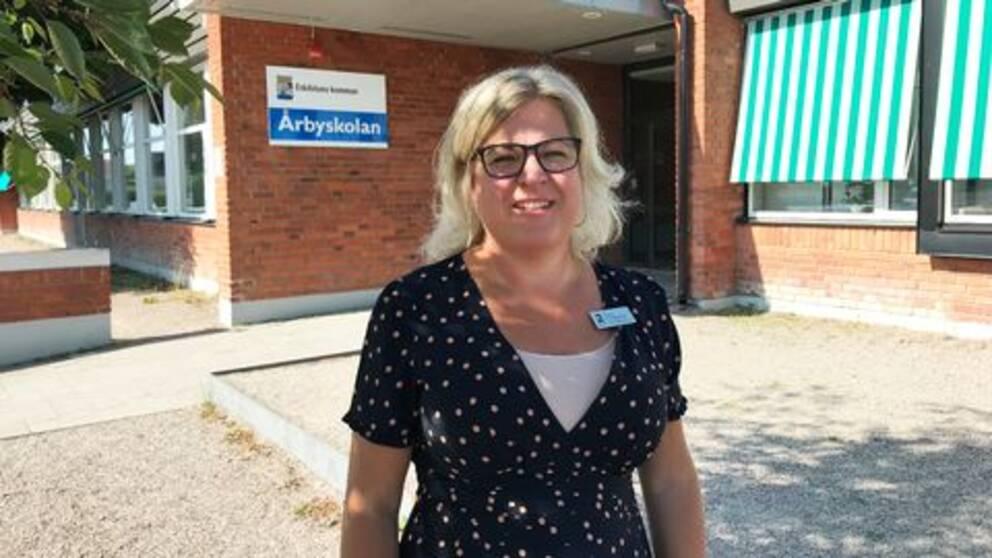 Tf skolchef Carin Pärlesköld framför Årbyskolans entré.