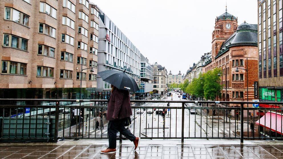Arkivbild på person som går i regn med paraply.