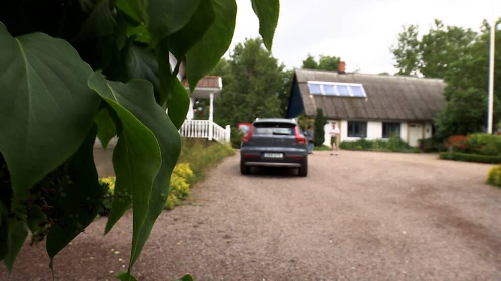 Gårdsuppfart med bil parkerad.