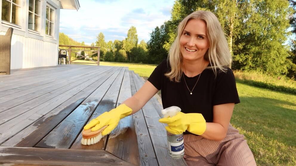Ellinor Sirén som driver Ekotipset skrubbar verandan med ättika-medel.