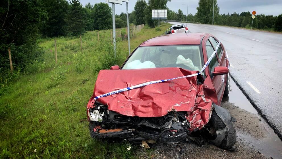 En demolerad bil med ett av polisen avspärrningsband över huven.