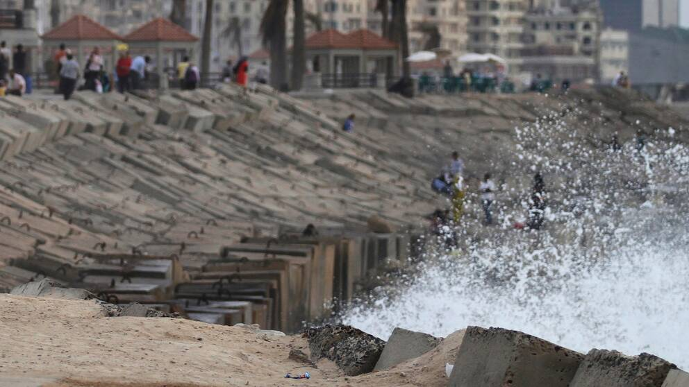 Stenpir på strand i Alexandria (arkivbild). Skummande vatten slår upp mot de stora stenarna.