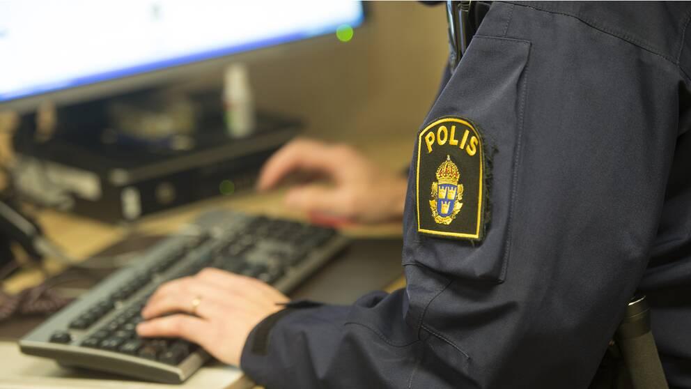 En polis arbetat vid en dator.
