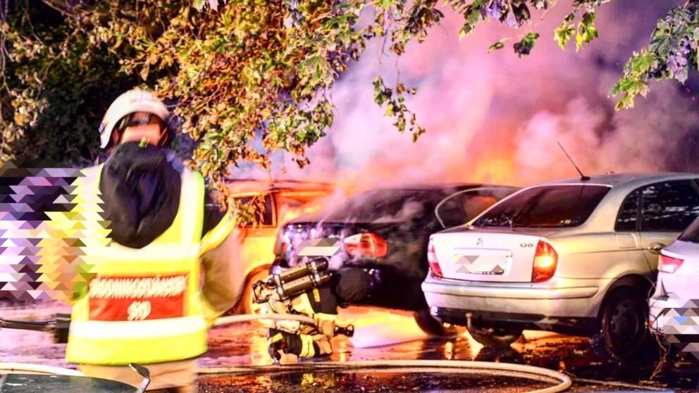Brinnande bilar. Brandmän i förgrunden.
