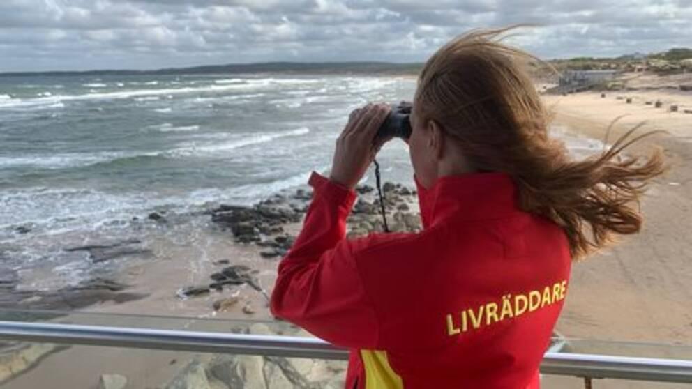 På bilden syns en kvinnlig livräddare med brunt hår kika över Tylösands strand och kust. Hyfsat kraftiga vågor syns.