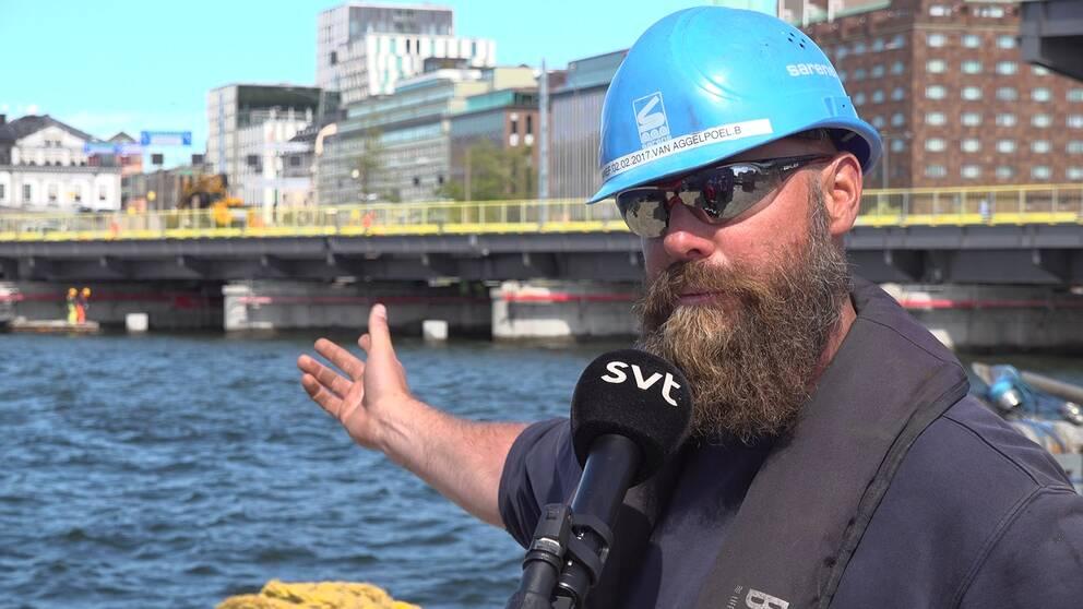 Man med blå bygghjälm står invid vattnet med centrala Stockholm som fond. Han pekar mot den bro som monteras bakom honom.