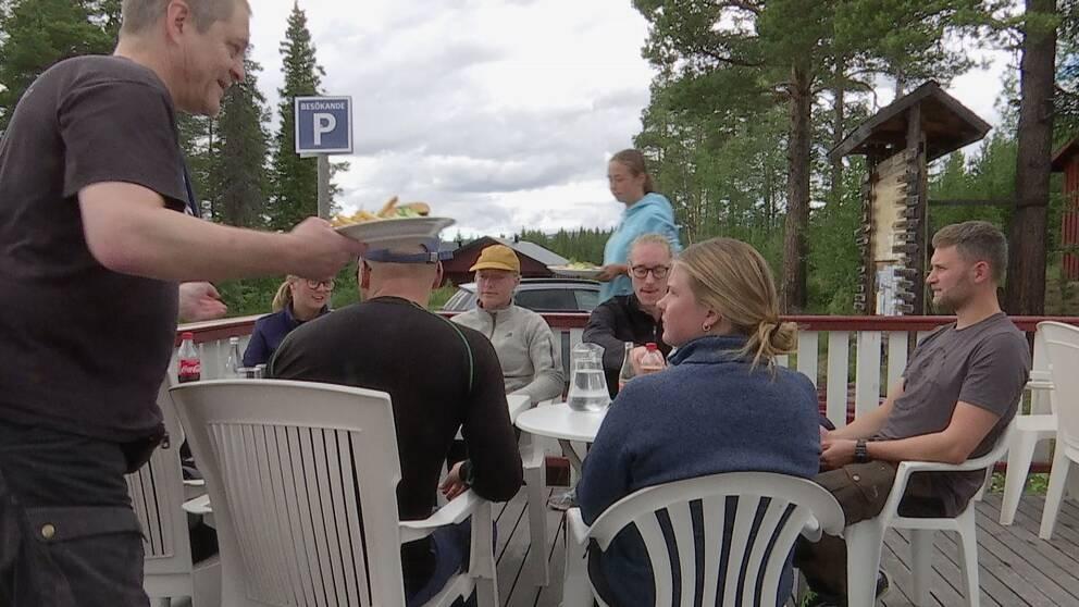 Ett sällskap på en uteserverkig serveras mat