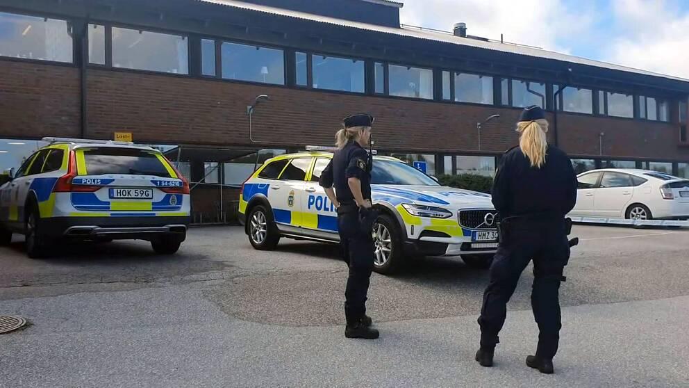 Två poliser i uniform framför två polisbilar.