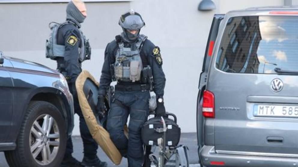 En polis med omfattande skyddsutrustning bär på en sköld. Intill honom står polisens piketbuss.