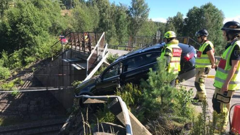 Räddningspersonal med gula reflexvästar står intill en bil som hänger ner över ett tågspår.