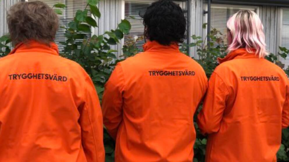 Tre trygghetsvärdar i orange jacka med texten – trygghetsvärd.
