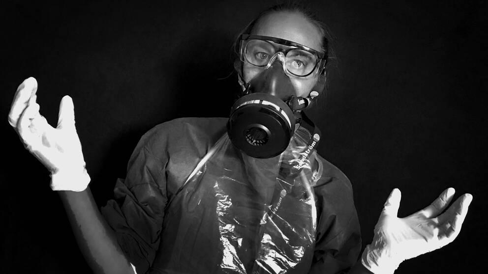 svartvit bild på kvinna i vårdkläder med handskar, glasögon, andningsmask och plasthandskar