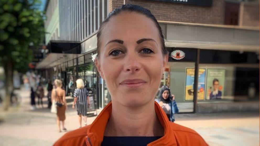 En kvinna i orange jacka
