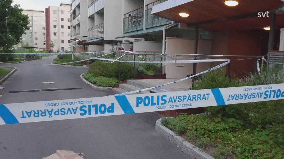 Bostadsområde i bakgrunden med av polisen uppsatt avspärrningstejp i förgrunden.