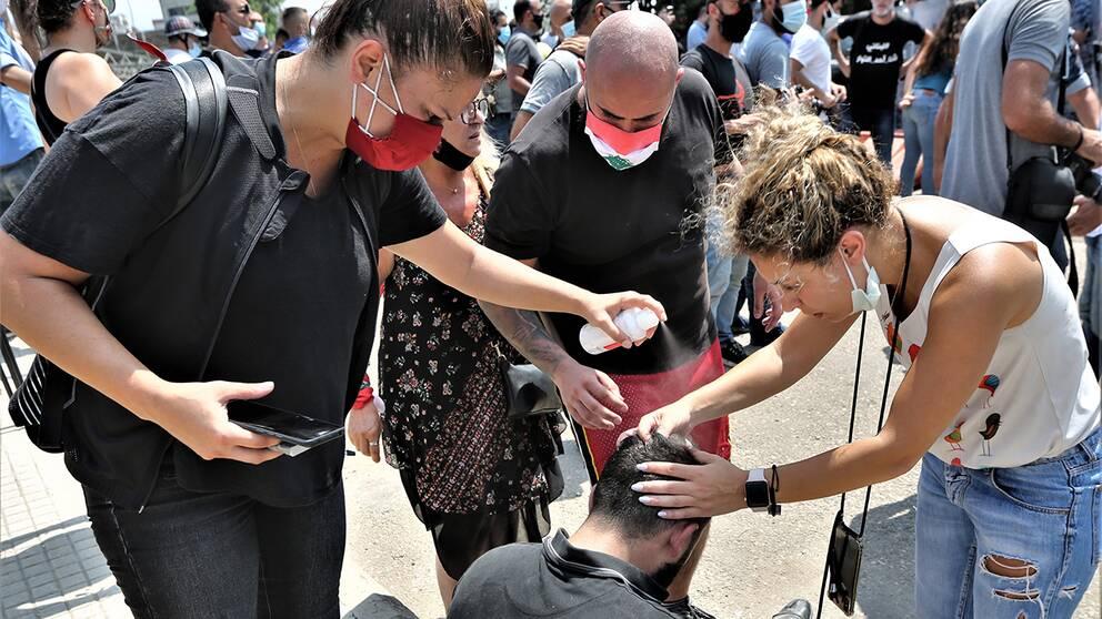 Demonstranter hjälper en annan med en huvudskada.