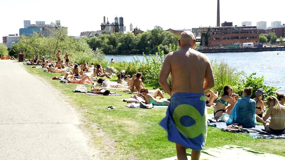 Många människor som solar vid vattenbrynet i Stockholm