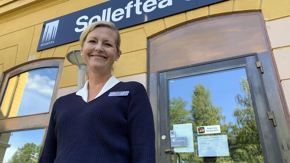 Monika Karlström, rektor vid Sollefteå gymnasium, ler mot kameran, ståendes framför skylten till Sollefteå gymnasium. Hon är iklädd en mörkblå stickad tröja och har en vit krage.
