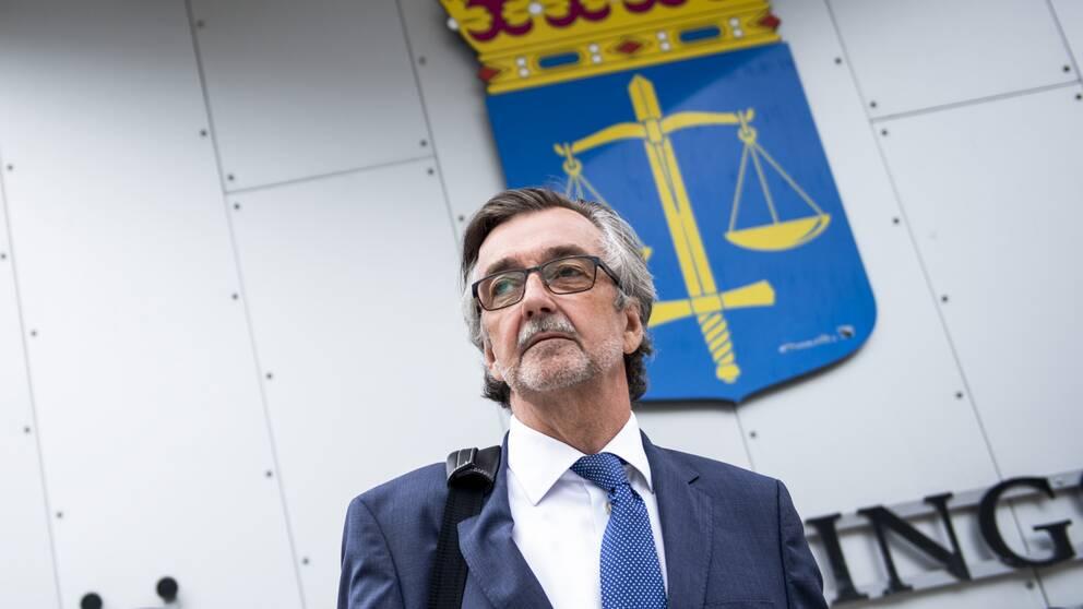 försvarsadvokat Gunnar Falk står framför domstolssymbolskylt med vågskålar