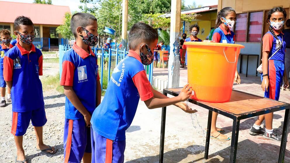 Elever i en grundskola i Dili i Östtimor som tvättar händerna när deras skola öppnar efter att ha varit stängd under corona-pandemin.