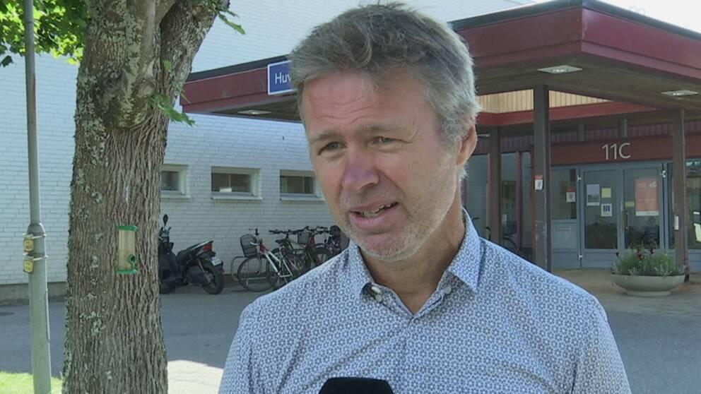 Stephan Stenmark intervjuas utomhus bredvid ett träd. Han har en ljusblå skjorta på sig.
