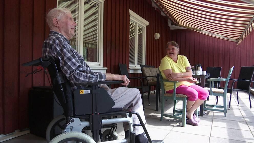 En äldre man i rullstol och en kvinna i färgglada kläder sitter och samtalar
