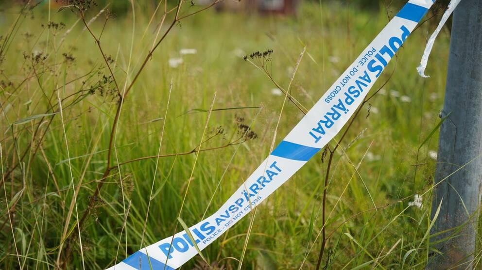 Ett polisavspärrningsband knutet i lyktstolpe har ramlat ner i gräset vid brottsplatsen
