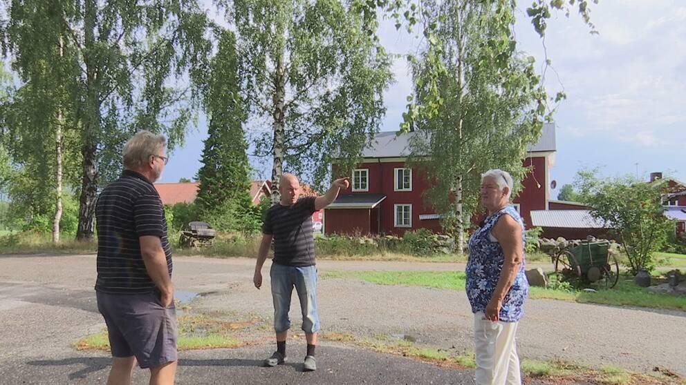 tre personer står på väg i bym sommartid