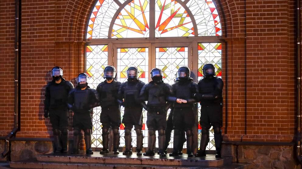 Säkerhetsstyrkor blockerar entrén till en kyrka under protester på Självständighetstorget i Minsk.