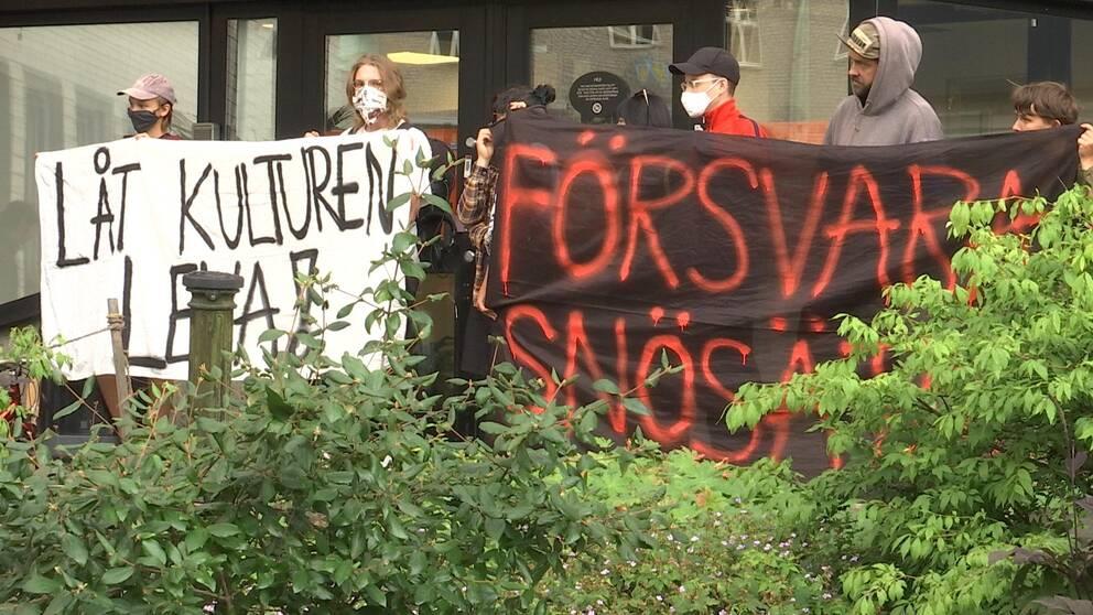 """Maskerade demonstranter håller banderoller med texterna """"Låt kulturen leva"""" och """"Försvara Snösätra""""."""