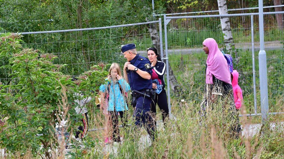 En polis står på en gång- och cykelväg i ett grönområde. Runt honom står fyra personer i olika åldrar.