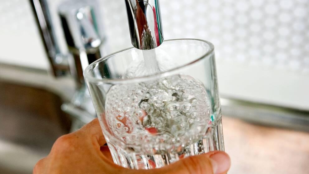 Vattenglas som fylls på i en kran.