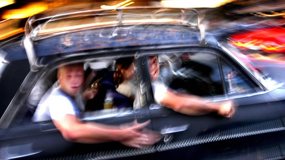 Glada bilåkare håller ut armarna genom bilfönstret och hamrar med händerna på plåten.