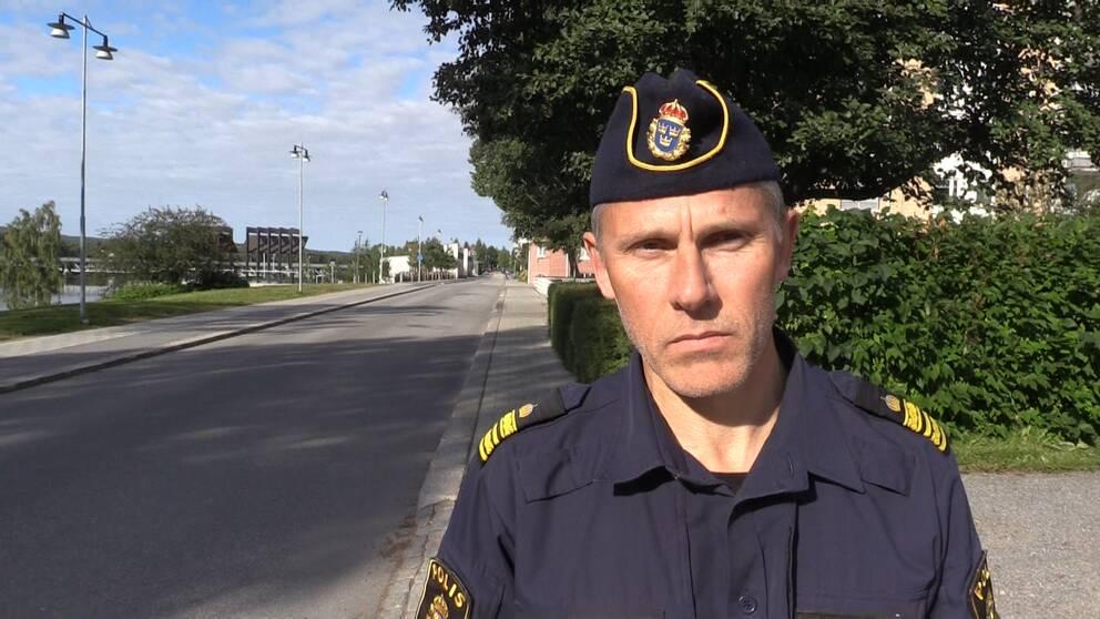 En polisman i tillhörande mössa tittar in i kameran.
