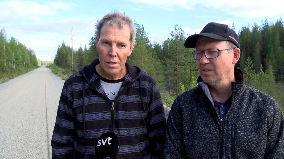 Två män på står på väg i skogen