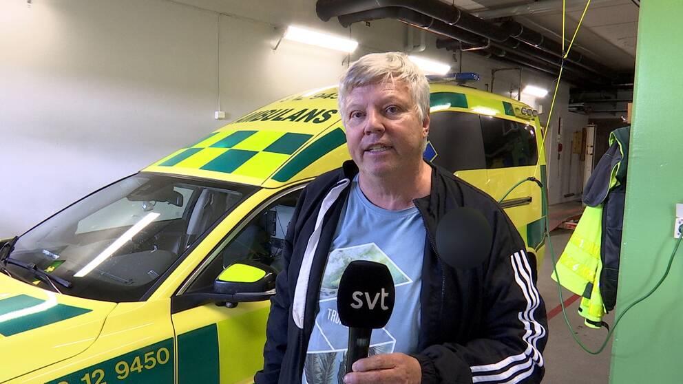 SVT:s reporter Anders Öhlund står framför en ambulans i ambulansgaraget