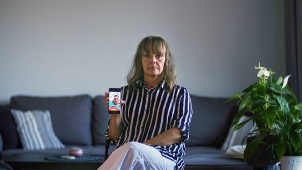 Lena håller upp en mobil med bild på den man hon trodde sig lärt känna på nätet.