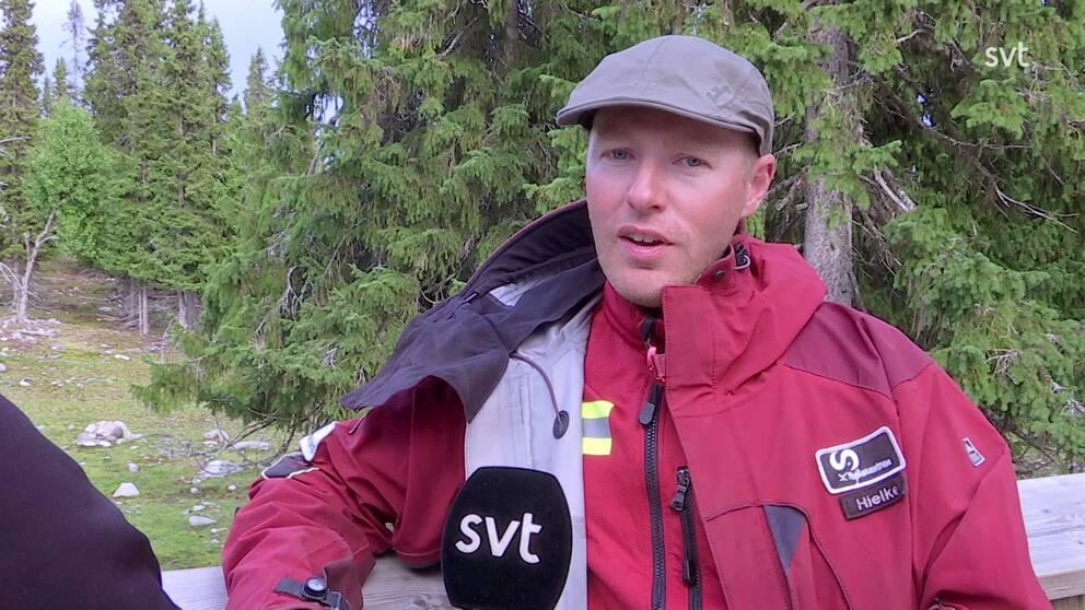 en man intervjuas vid hägnet, skog i bakgrund