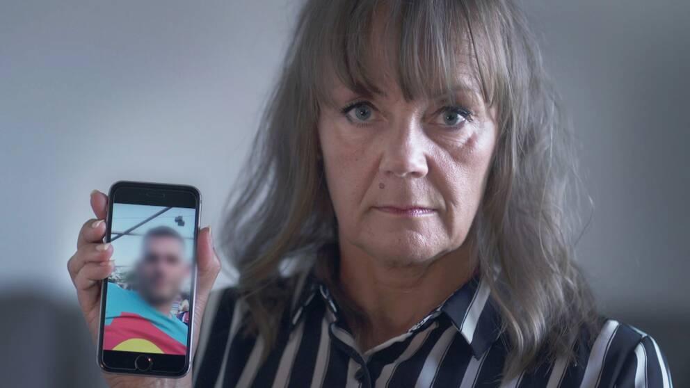 Lena håller upp en mobil med bild på en man som en nätbedragare använt för att lura henne på pengar.