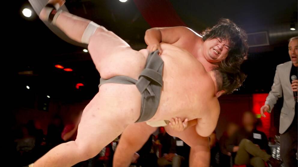 Två sumobrottare i ringen, den ena får den andre på fall.