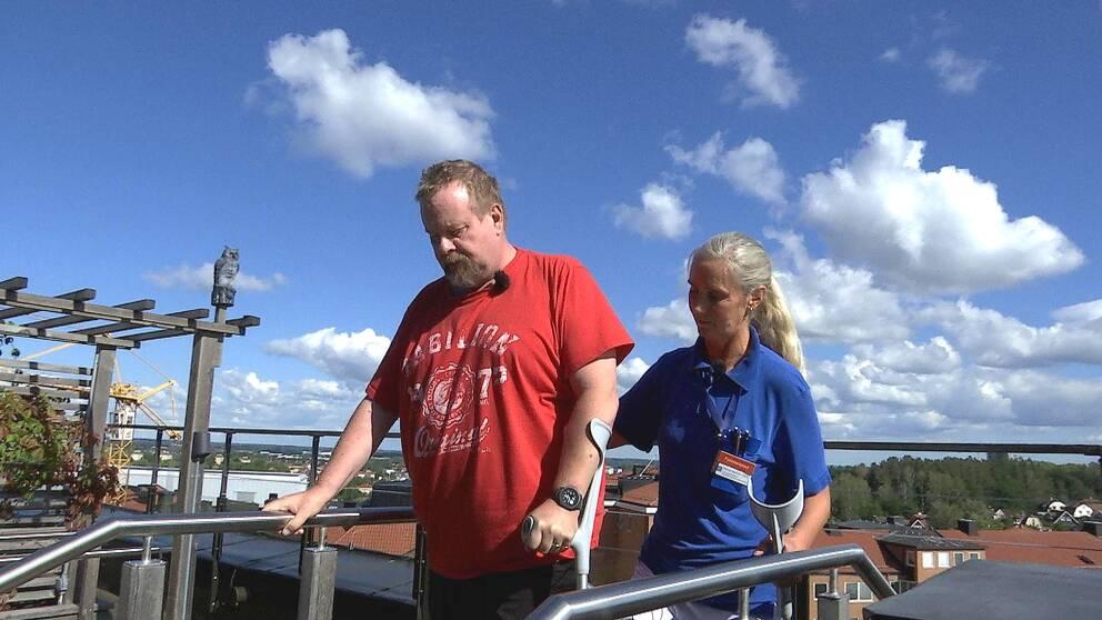 Johan står på en liten trappa uppe på en takterass med en molning himmel bakom. Han har kryckor och ansiktet är sammanbitet. Bredvid honom står fysioterapeuten Marina med en hand på hans rygg.